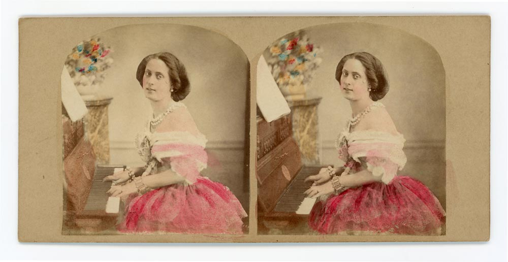 Vintage hand tinted stereo card of a woman playing the piano