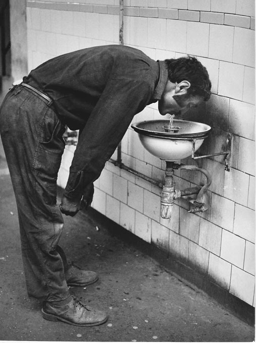 Gelatin silver print of factory worker at a drinking fountain