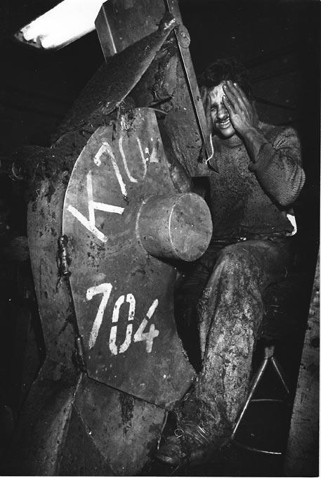 Gelatin silver print of a man operating machinery