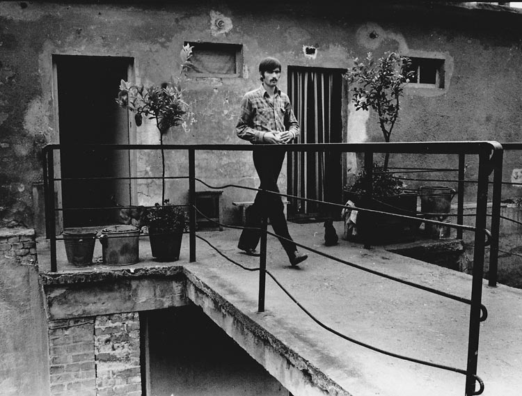 Gelatin silver print of man walking out of Hungarian house