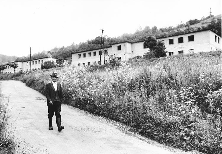 Gelatin silver print of a Roma man walking down village road