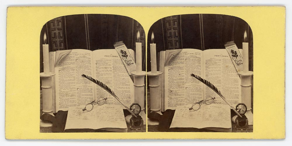Vintage stereo card still life with an open book, glasses and quill pen