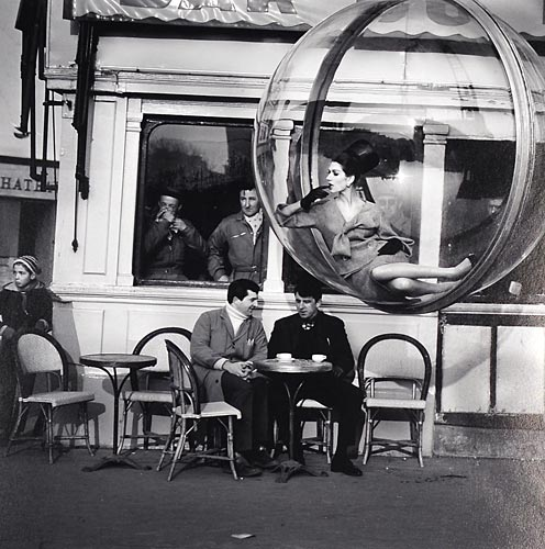 Fashion model floating in a bubble in front of a Paris cafe