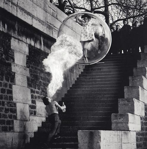 Fashion model floating in a bubble over stairs with man blowing smoke
