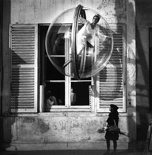 Fashion model floating in a bubble in front of Paris window