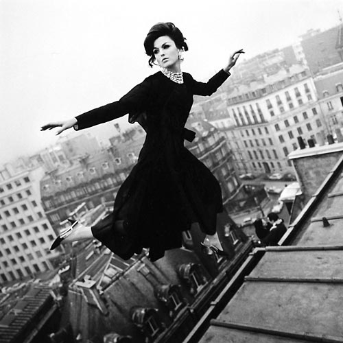 Fashion model flying over Paris buildings