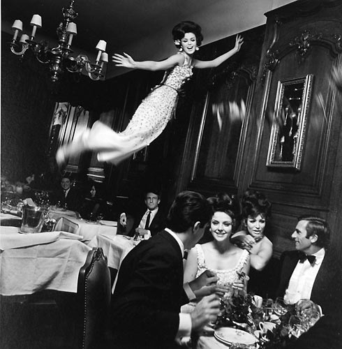 Fashion model flying over dinner guests